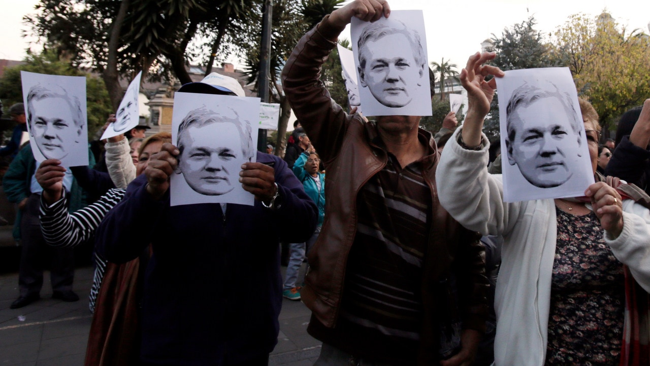Ecuadoreans hold pictures of Julian Asssange  during a demonstration to support him.