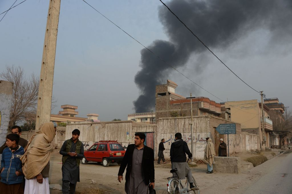 Afghan civilians gather on a street next to a plume of smoke coming from the area around an office of the British charity Save the Children.