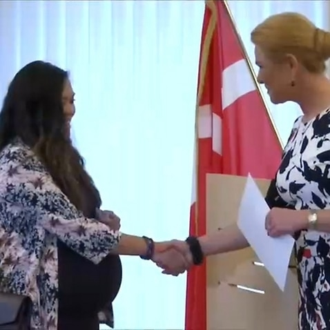 Denmark's Immigration Minister Inger Stojberg shakes hands with a new citizen