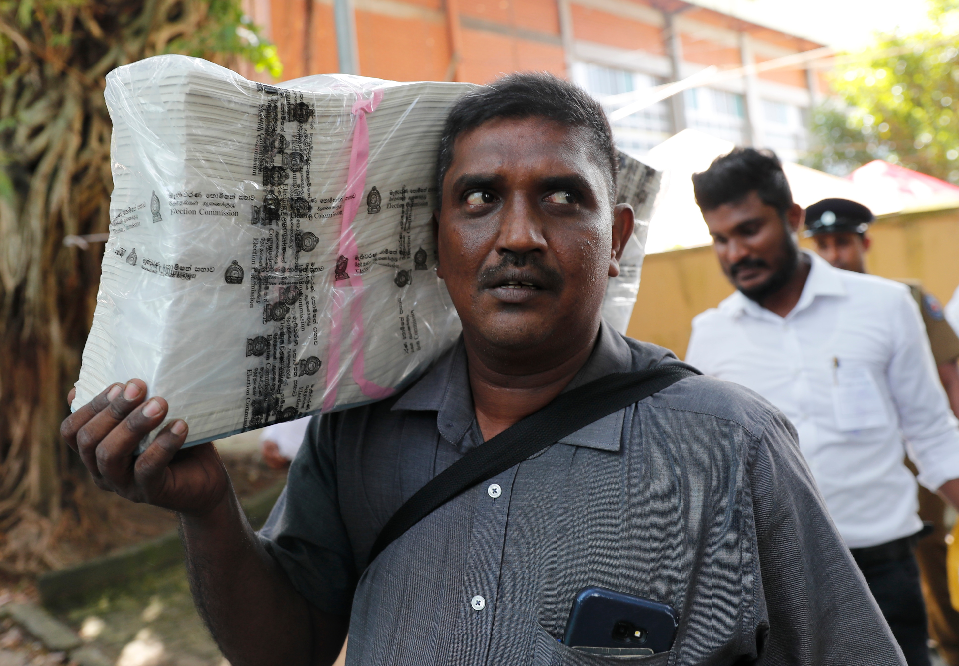 A Sri Lankan polling worker carries ballot papers outside a polling material distribution center in Colombo.