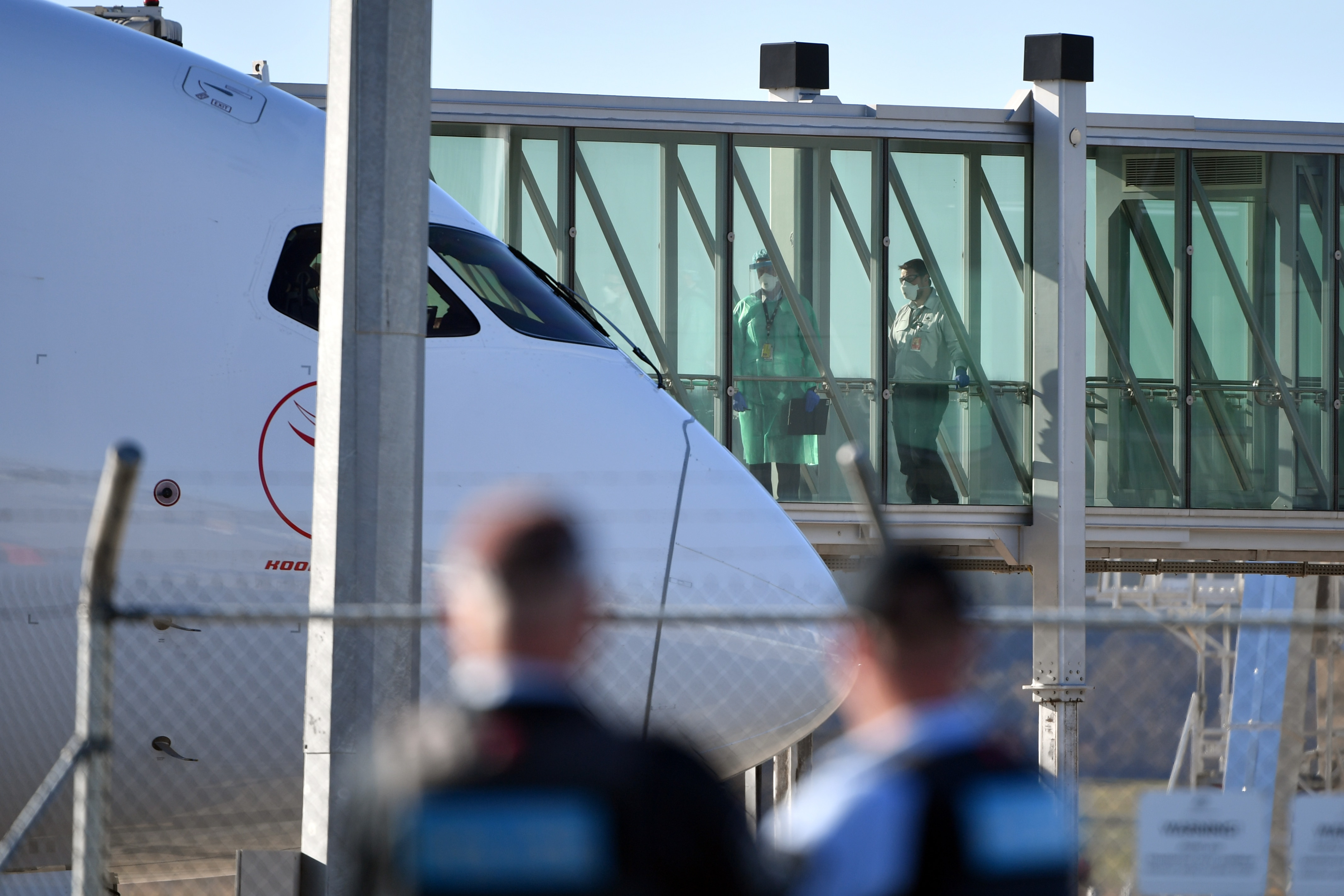 Health officials wait for Australians stranded in India to disembark a Qantas plane at Canberra Airport in May.