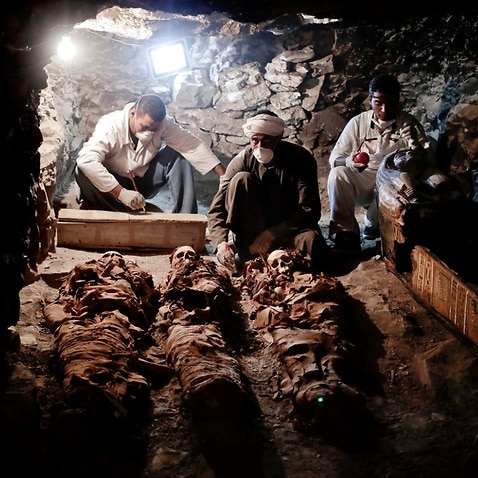Archaeologists work on mummies found in the New Kingdom tomb that belongs to a royal goldsmith in a burial shaft, in Luxor, Egypt, Saturday, Sept. 9, 2017.