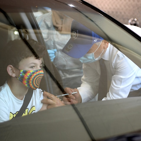 Dr Jamal Rifi administers a Covid vaccine to 12 year old Bailee Little at a pop-up drive through vaccination clinic at Belmore Oval, in Sydney, Friday, September 17, 2021.