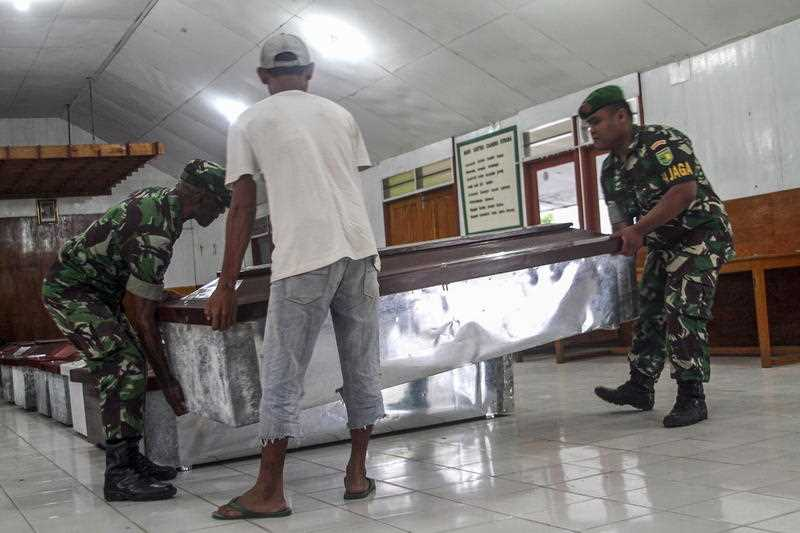 Indonesian military personnels and workers prepare coffins for construction workers, who were shot dead by suspected separatists, at a hall in Wamena, Papua.