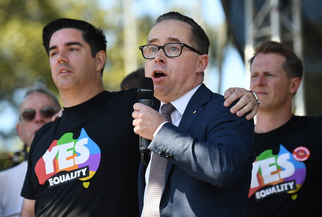 Alan Joyce, the CEO of Qantas, stands with his partner as he speaks after watching the same sex marriage vote result announcement