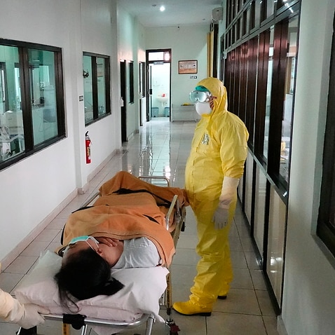 Health workers in protective suits take part in a drill in handling coronavirus cases at a hospital in Denpasar, Bali.