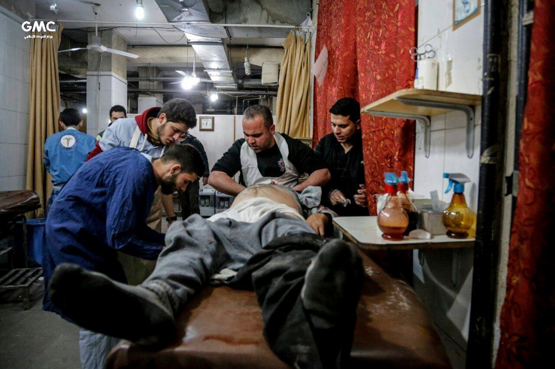 Syrian paramedics treat an injured man who was wounded by the shelling of the Syrian government forces, at a makeshift hospital, in Ghouta.