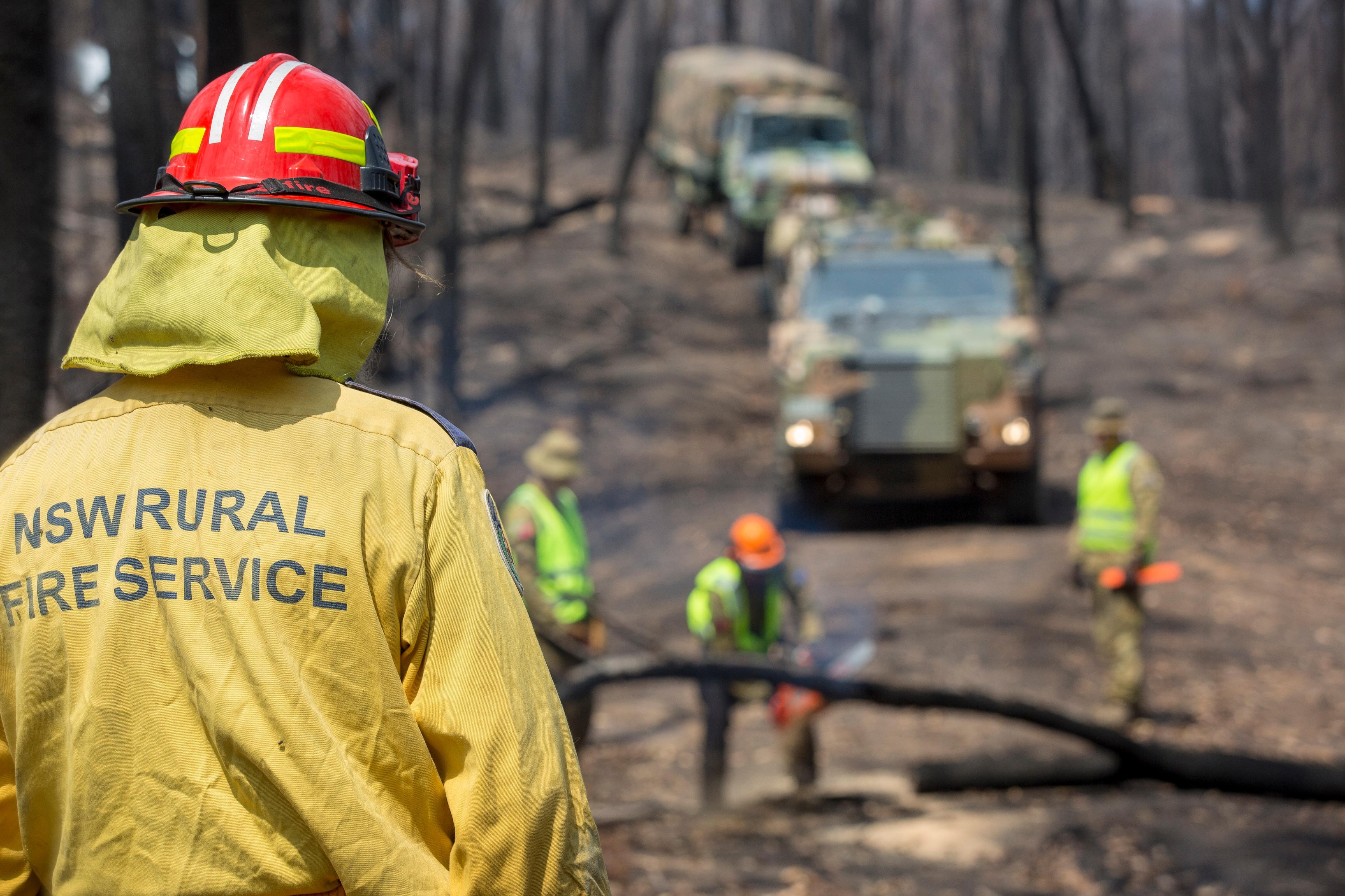 Rural Fire Service crews and Australian Army troops clear a fire break in regional NSW.