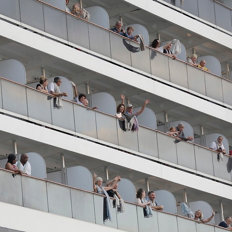 Passengers wave from the MS Westerdam cruise ship at a seaport in Preah Sihanouk province, Cambodia, 14 February 2020.