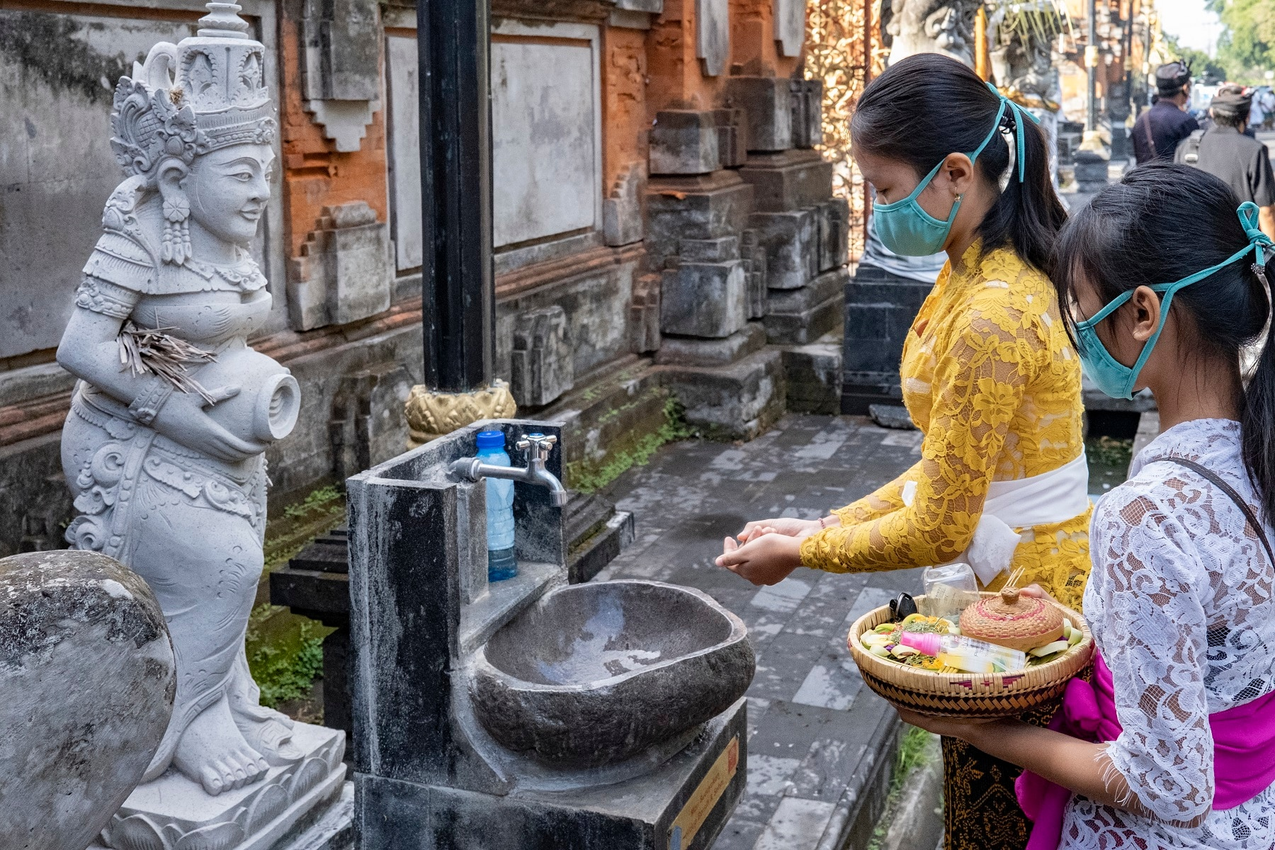 A Balinese woman washes her hands before entering a temple during Saraswati ceremony in Bali, Indonesia.