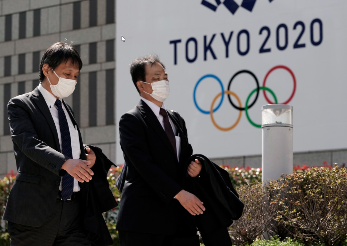 Office workers wearing masks walk past the emblem of Tokyo 2020 Olympics.
