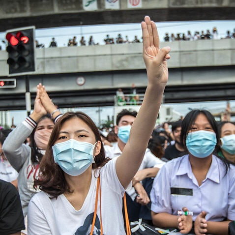 A pro-democracy protester seen making the three finger salute during an anti-government demonstration in the Thai capital.