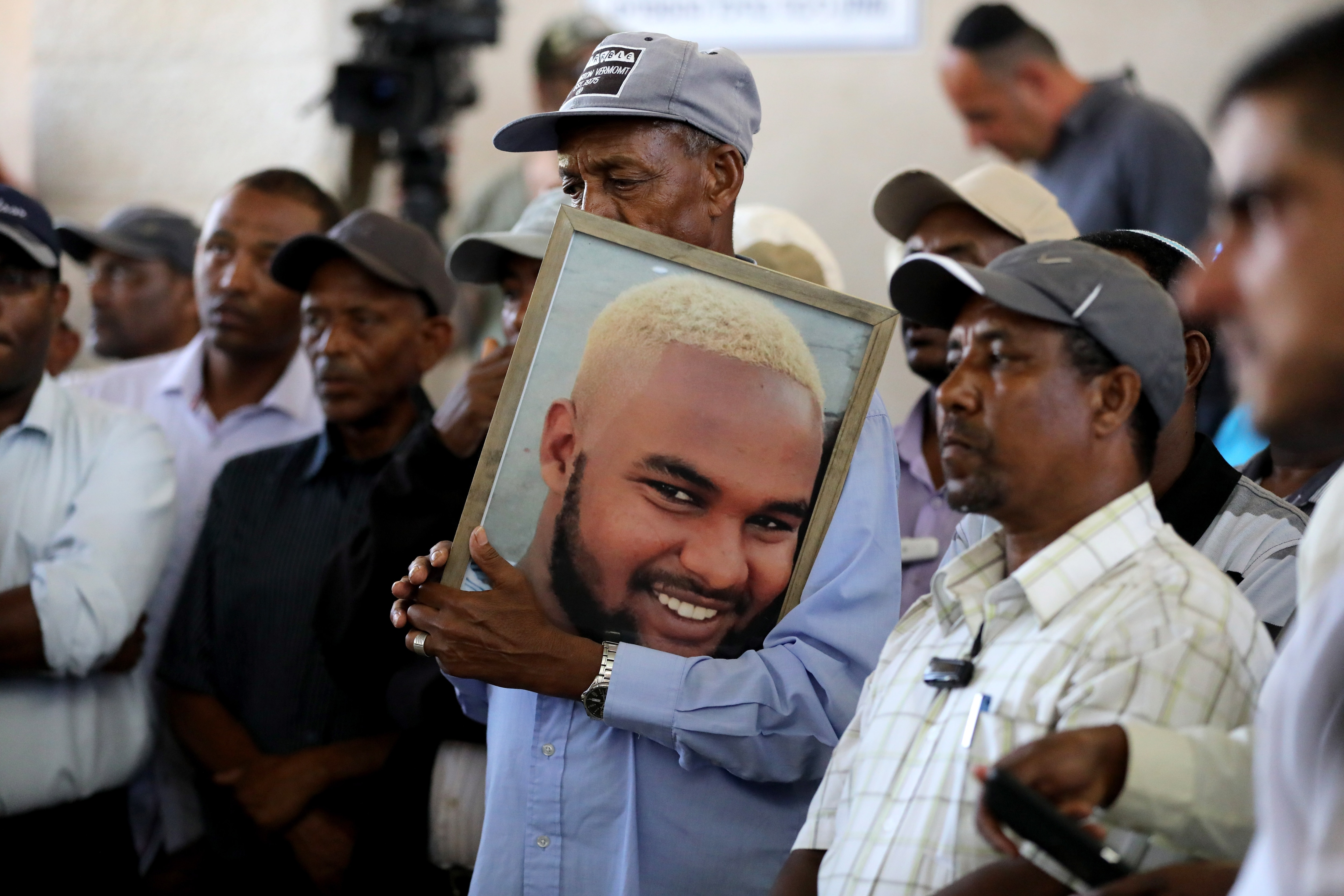 Family members and friends hold a picture and mourn Solomon Tekah, Israel, 02 July 2019.