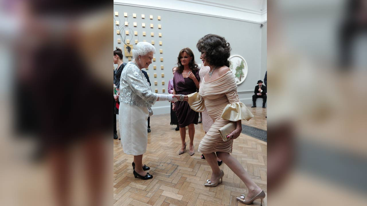 Joan Collins curtsying as she meets Queen Elizabeth II during a Diamond Jubilee celebration
