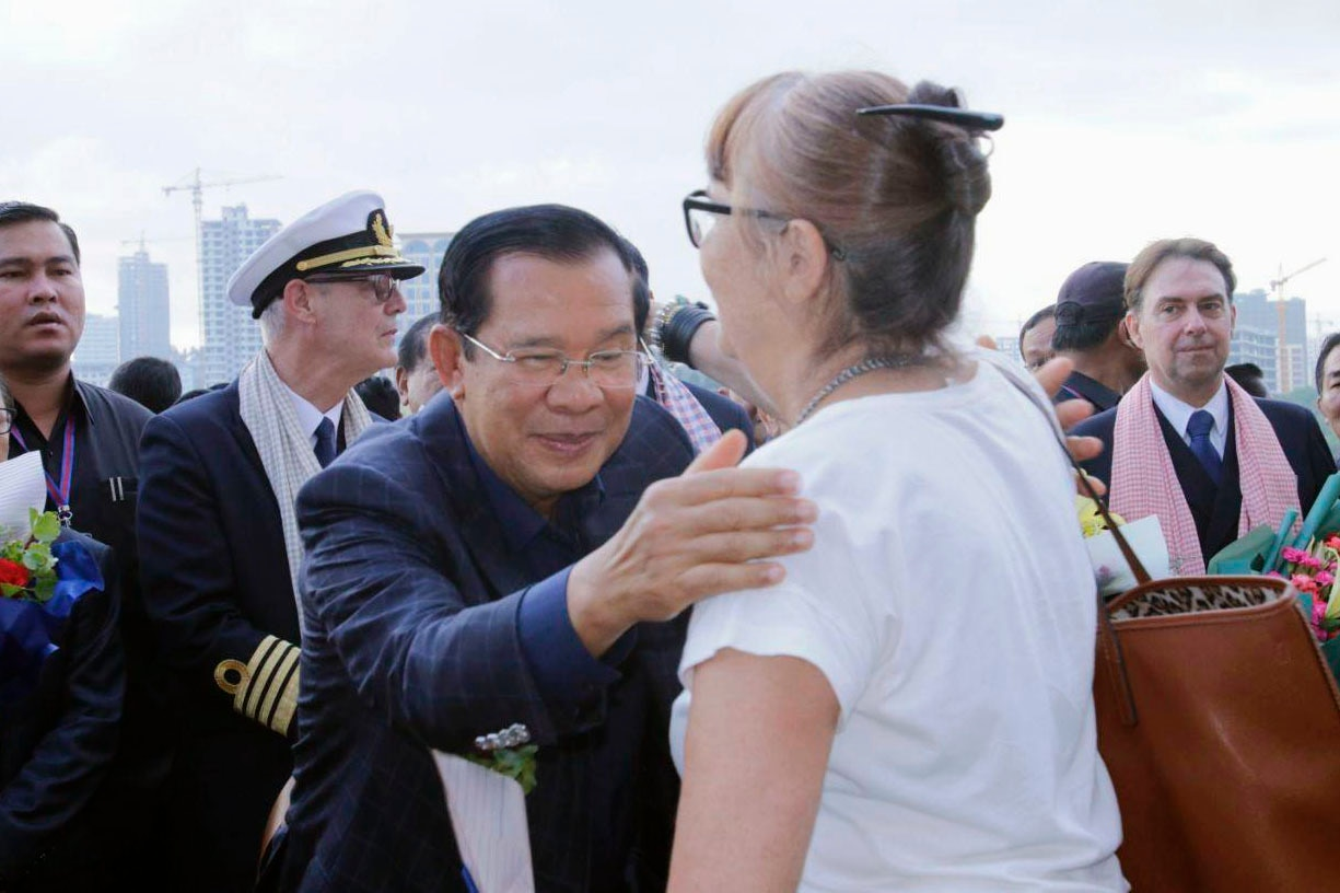 Cambodian Prime Minister Hun Sen (C) greeting a passenger of the Westerdam cruise ship that was turned away from at least five ports over coronavirus fears.