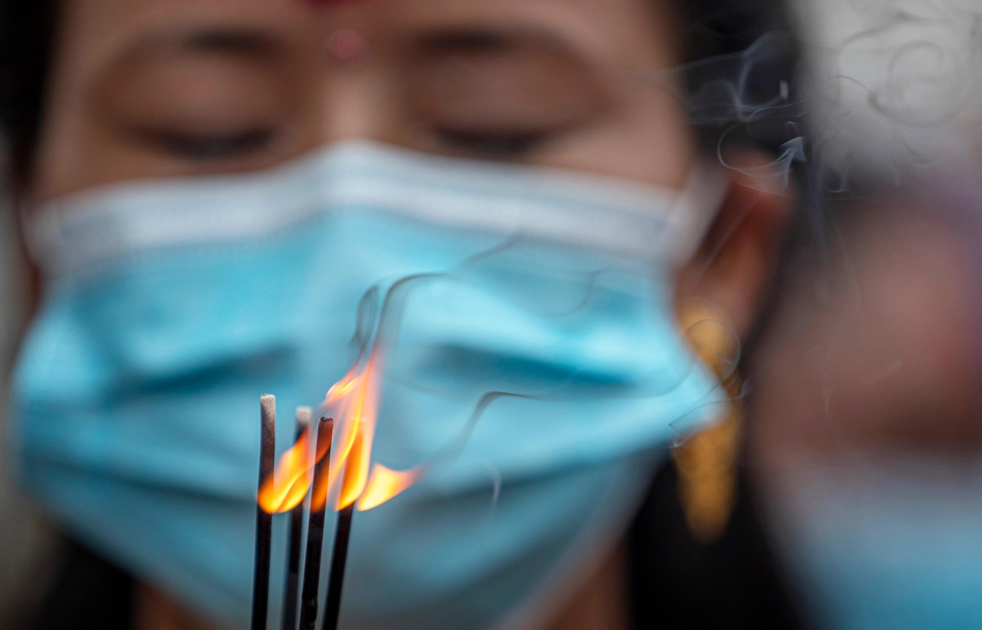 A woman wears a face mask as she worships Lord Shiva (Hindu god of creation and destruction) to mark the Teej festival amid the coronavirus pandemic fear in Kathmandu, Nepal, 09 September 2021.