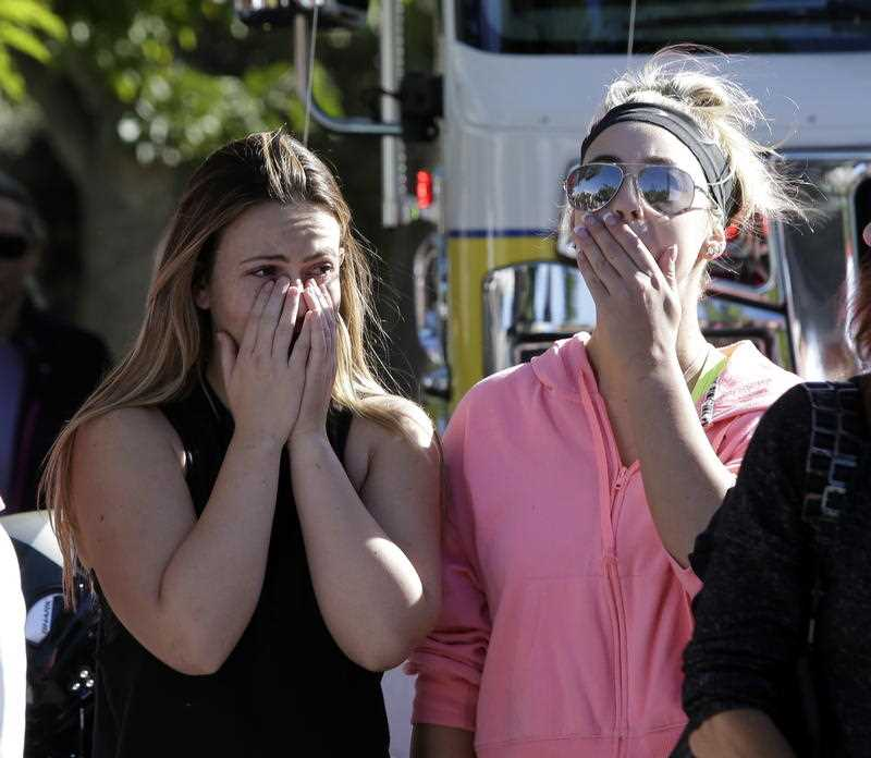 Alexis Tait, who lost a friend in the mass shooting at the Borderline Bar & Grill cries with Rachel Berg.