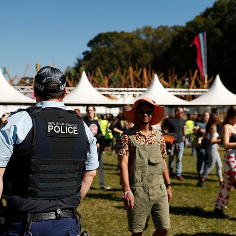 Police officers and drug detection dogs walk amongst festival goers by an entrance to Splendour In The Grass 2019 on July 19, 2019