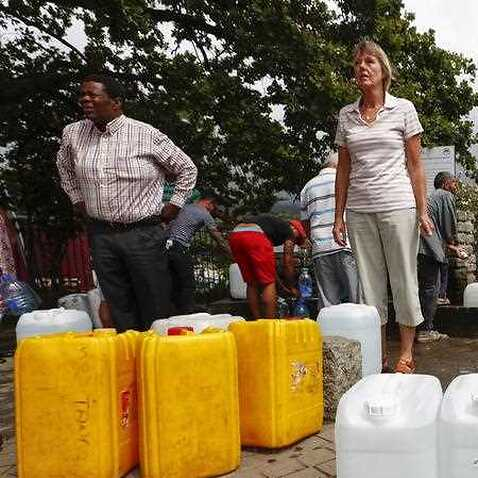 Residents of Cape Town collect drinking water from a mountain spring collection point in Cape Town, South Africa, 19 January 2018
