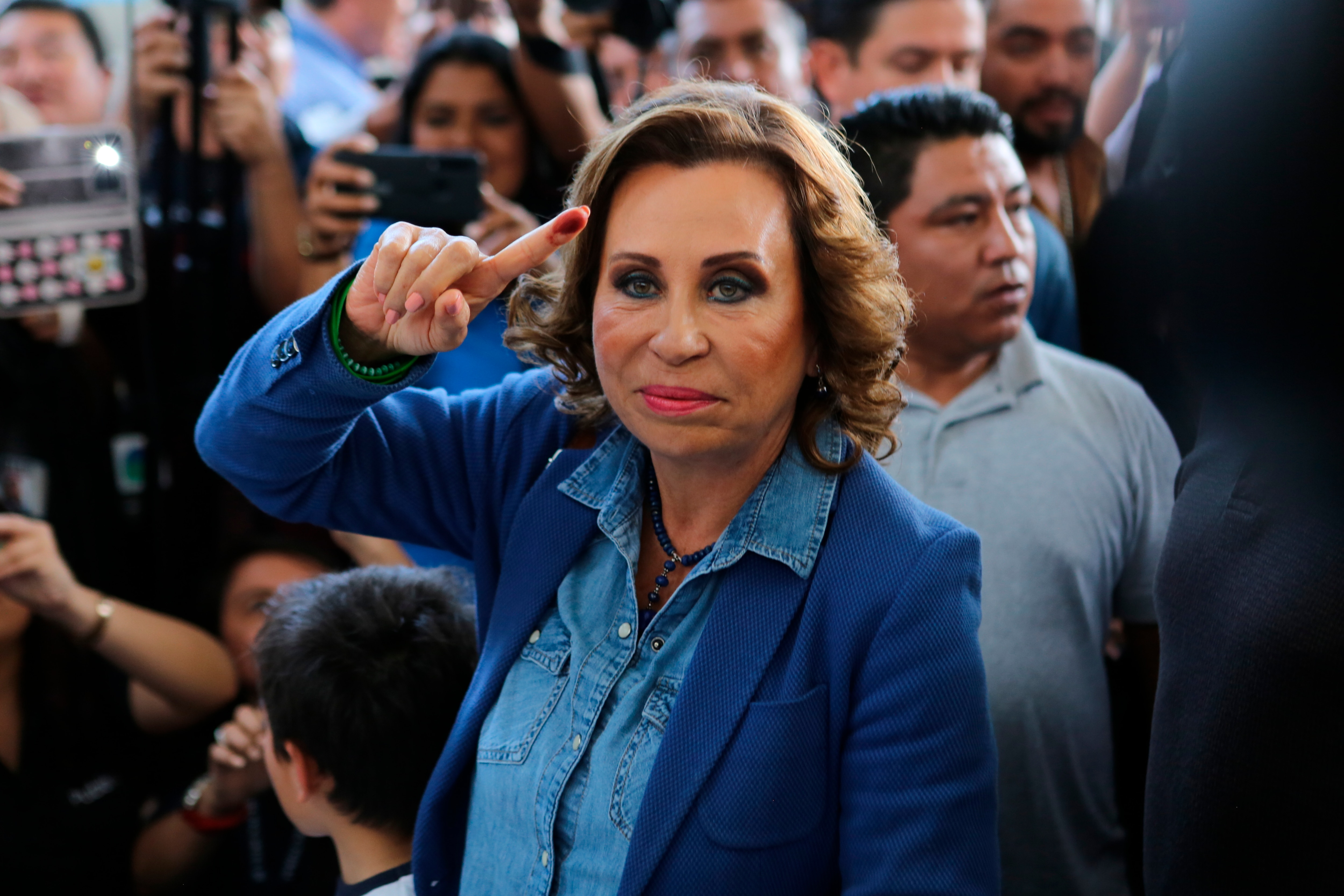 Former first lady turned presidential candidate Sandra Torres shows her ink-stained finger after casting her vote.