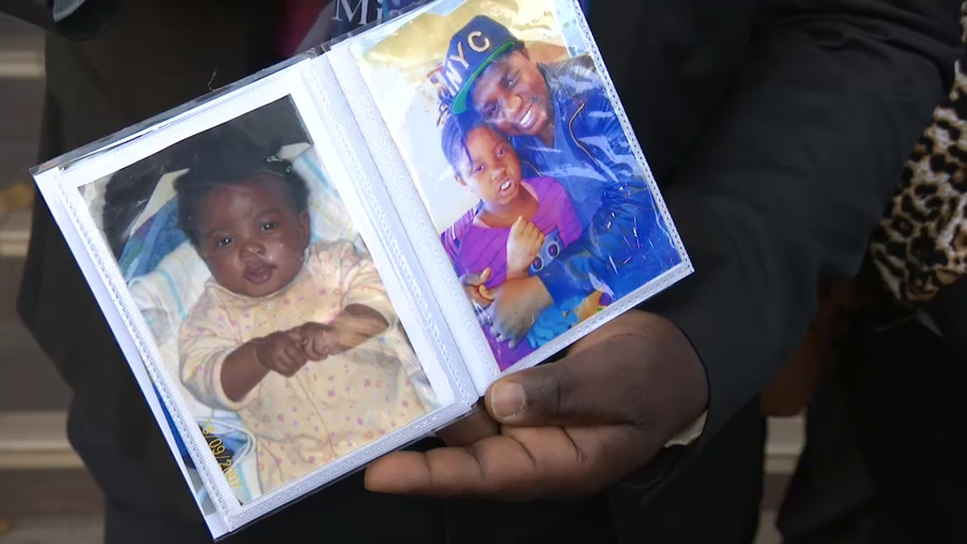Parents show photos of the late nine-year-old Miata Jibba outside the State Coroner's Court.