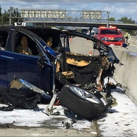 Emergency personnel work a the scene where a Tesla electric SUV crashed into a barrier on U.S. Highway 101 in Mountain View, Calif.