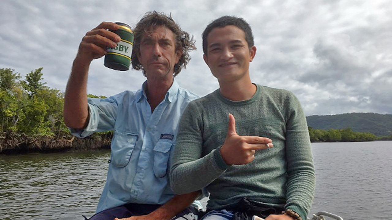A local fisherman (left) treating one of two suspected asylum seekers to a tour after being found on the banks of the Daintree River.