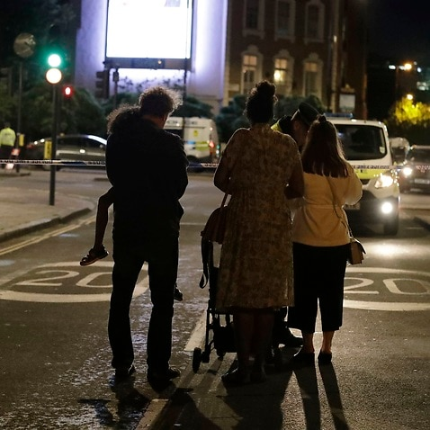 People wait by a cordon before being escorted through by police after the London attack.