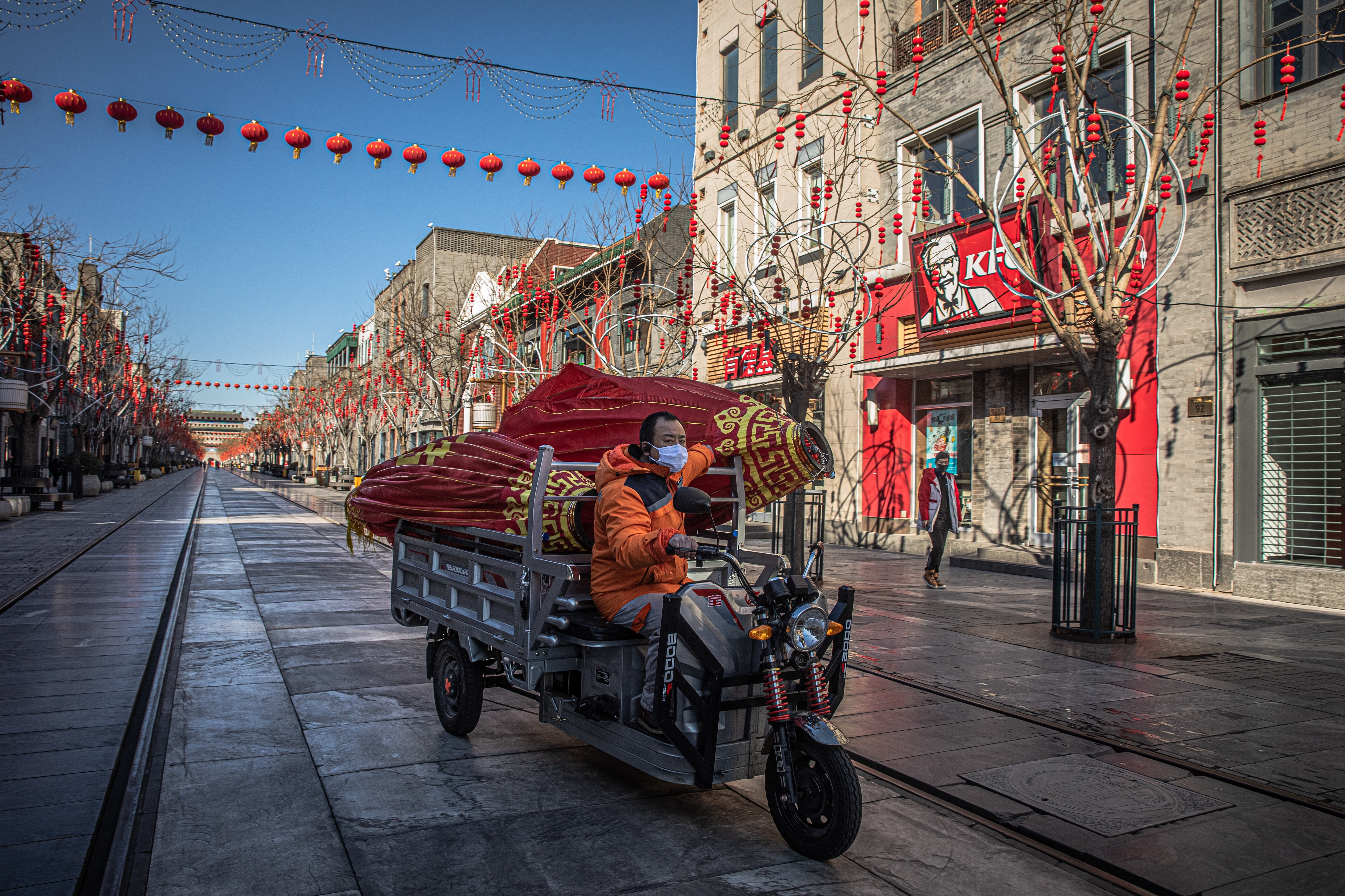 A worker wearing a protective face mask rides a three-wheeled vehicle on an almost empty pedestrian shopping street named Qianmen, in Beijing, China.