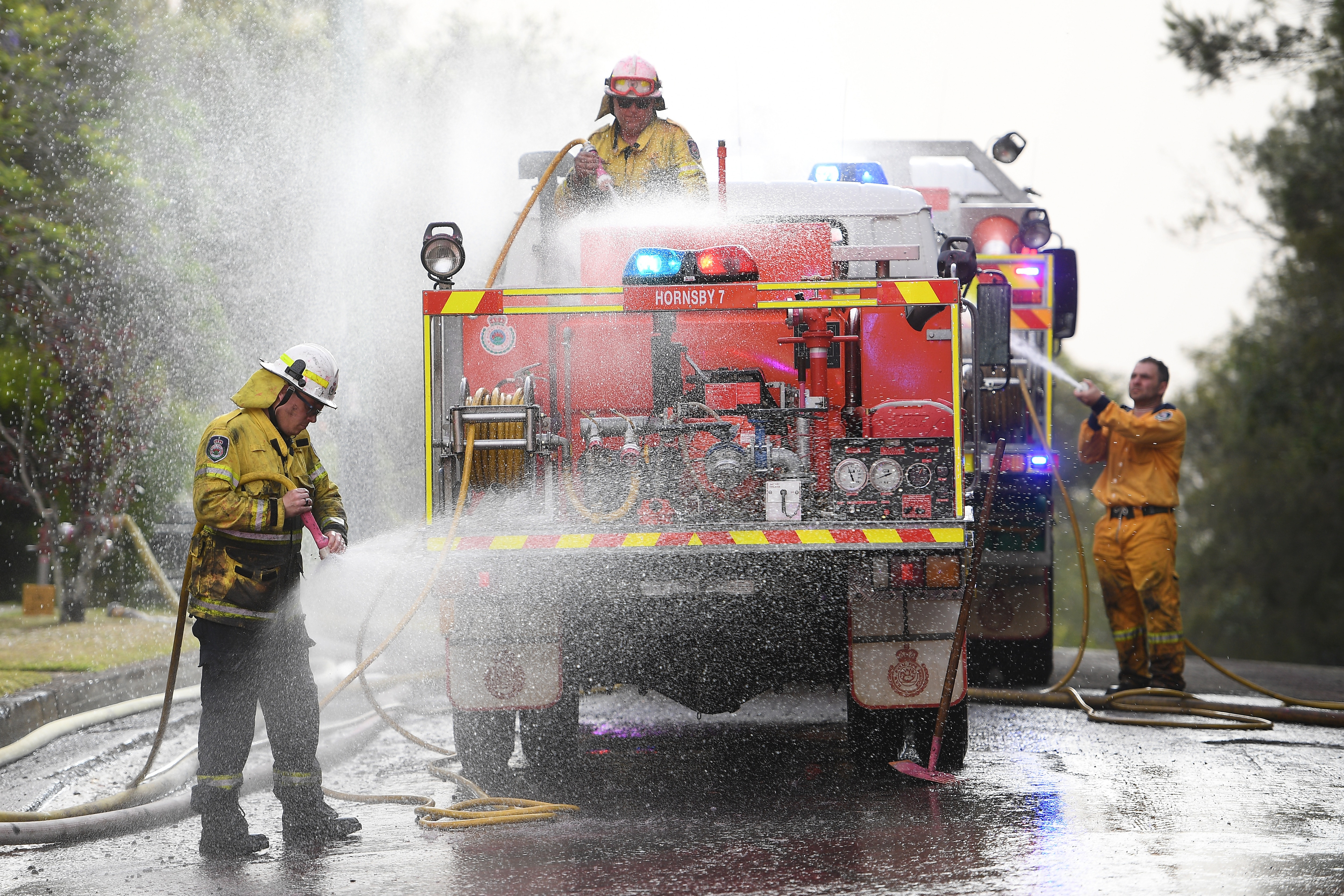 NSW Rural Fire Service crews wash chemical fire retardant off their truck after it was dropped to protect houses at South Turramurra, north of Sydney.