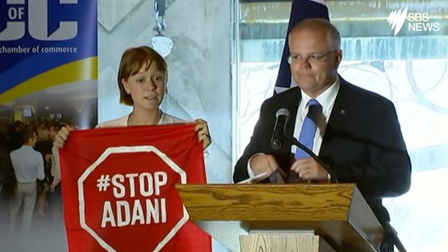 A Stop Adani protester takes to the stage
