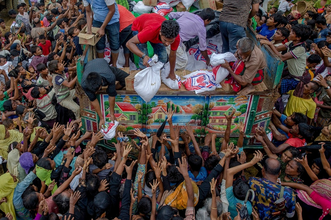 Rohingya Muslims, who crossed over from Myanmar into Bangladesh, reach out for food distributed by aid agencies in 2017.