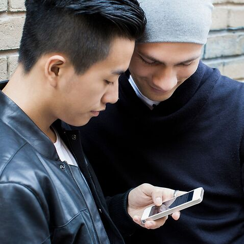 China, Hongkong, young male gay couple standing in street looking at smartphone