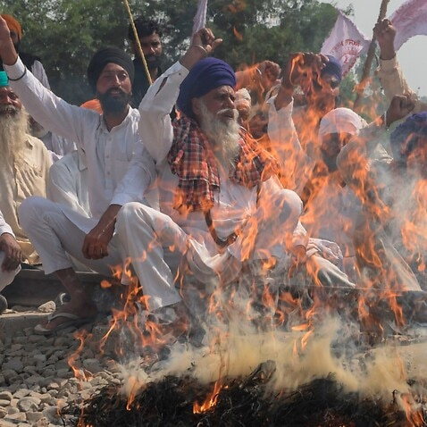 Farmers shout slogans while burning an effigy during a protest against the recent passing of agriculture reform bills in the Parliament,