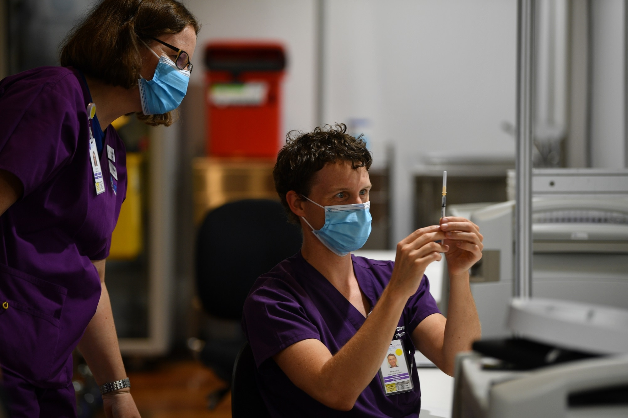 A healthcare worker is seen handling an AstraZeneca Covid-19 vaccination inside a vaccination centre.