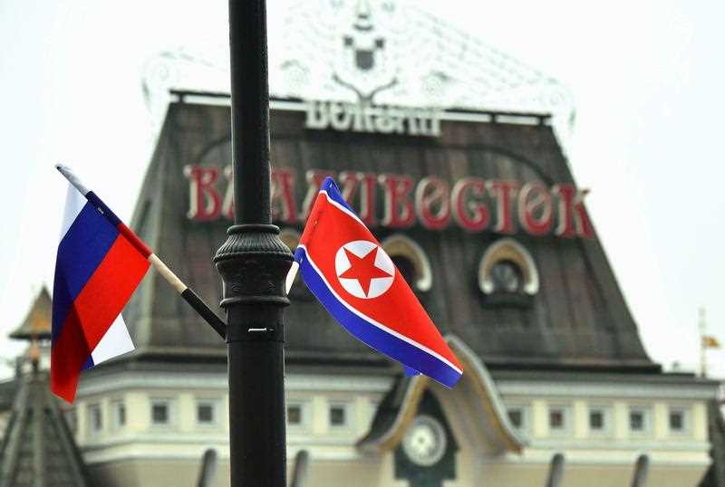 Russia and North Korean flags are seen near Vladivostok station.