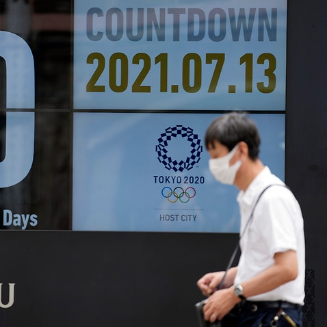 A man wearing a face mask against the spread of the coronavirus walks in front of a countdown calendar showing 10 days to start Tokyo 2020 Olympics Tuesday, July 13, 2021, in Tokyo. (AP Photo/Eugene Hoshiko)