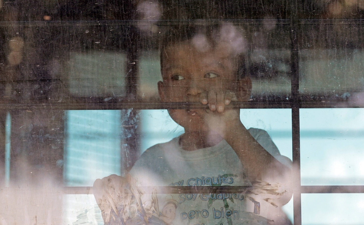 An immigrant child looks out from a U.S. Border Patrol bus leaving as protesters block the street outside the US Border Patrol Central Processing Center
