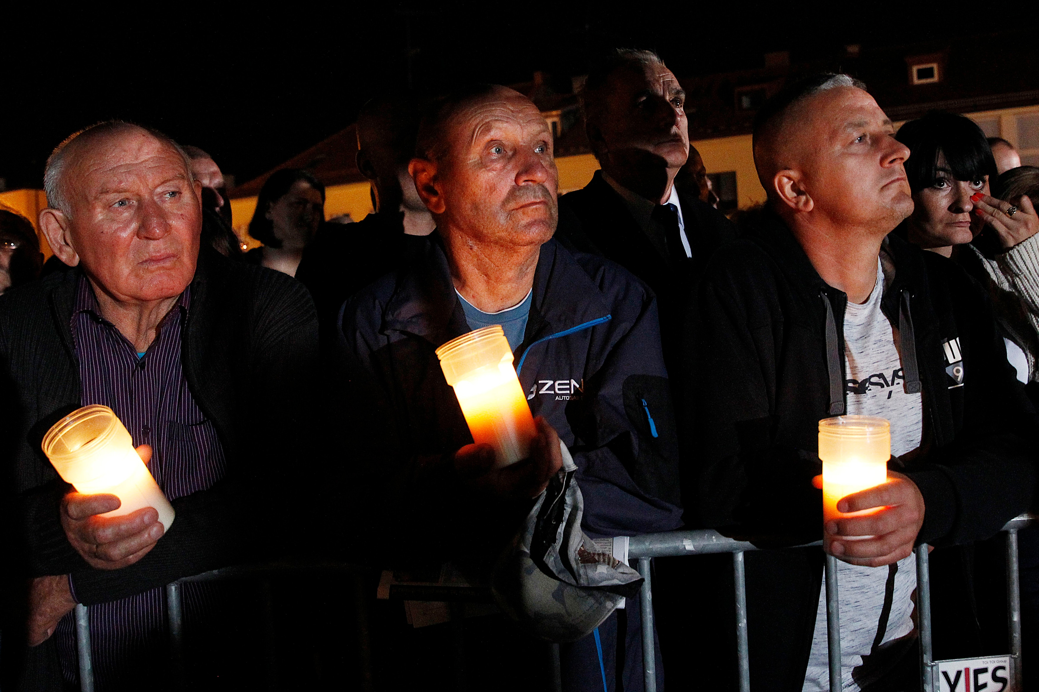Spectators hold candles in their hands at the memorial service during ceremony marking 80th anniversary of World War II.