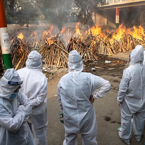 Visitors dressed in PPE suits watch as bodies are collectively lit at the converted parking lot of the Gazhipur cremation ground in New Delhi, India on April 28, 2021. A massive spike in Covid-19 cases and consequent deaths have overwhelmed  the cremation