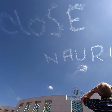 A man watches as a plane skywrites