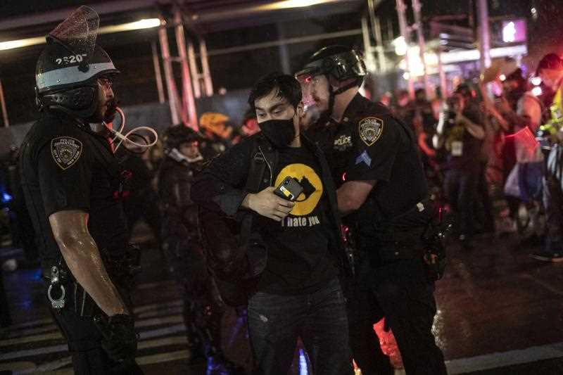 Police arrest protesters who had broken curfew on a marching through the Manhattan borough of New York
