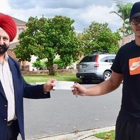Harmohan ingh Walia hands a cheque to student in Blacktown
