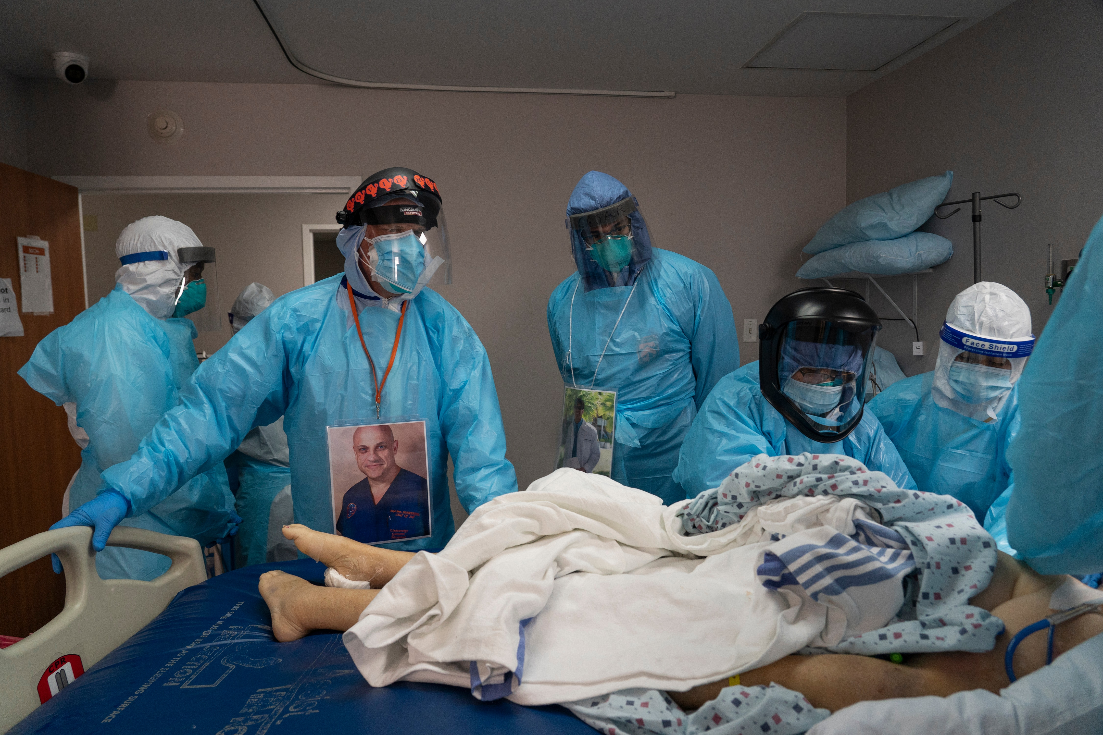 Dr Joseph Varon (2nd L) supervises the handling of a patient after death in the COVID-19 intensive care unit at the United Memorial Medical Center on in Houston