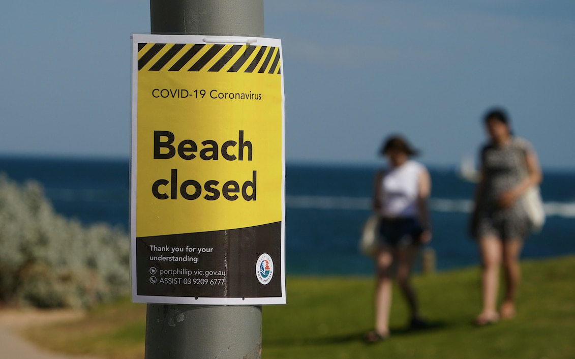 "A ""beach closed"" sign is seen at St Kilda Beach in Melbourne."