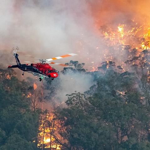 A firefighting helicopter battles a bushfire near Bairnsdale in Victoria's East Gippsland region.