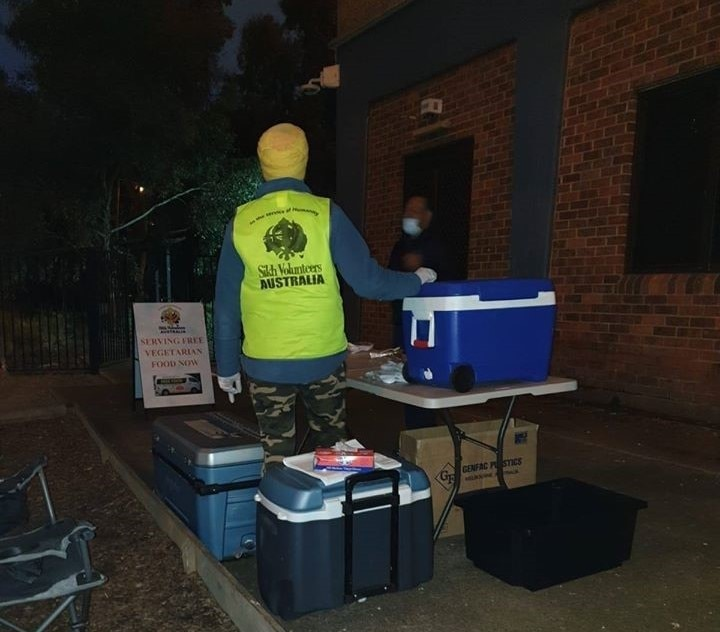A Sikh volunteer serving free meals at a public housing estate near Flemington on Sunday night.