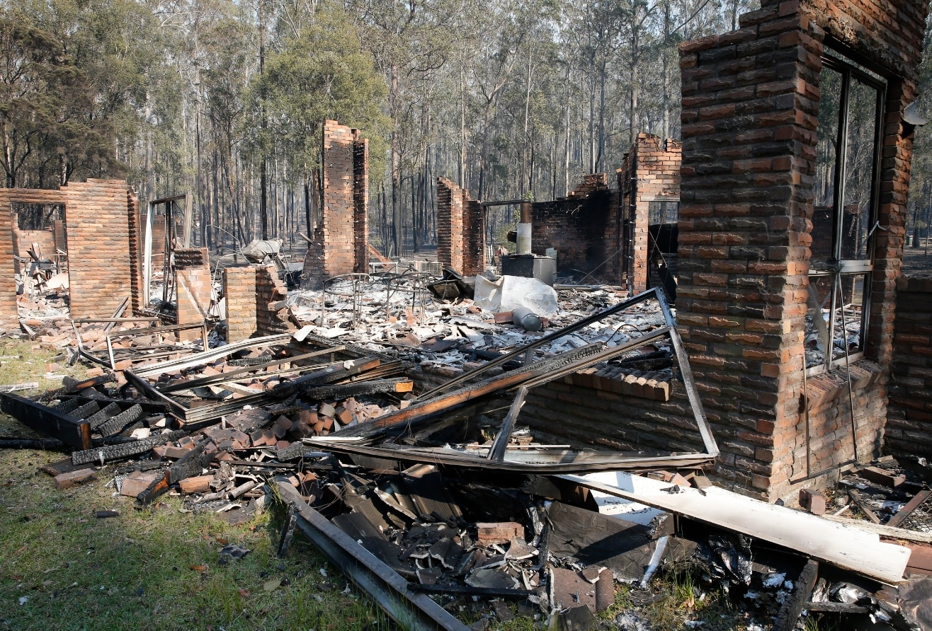 The remains of the residence at Four Paws boarding kennels smoulders along the Pacific Highway south of Taree, Saturday, November 9, 2019.
