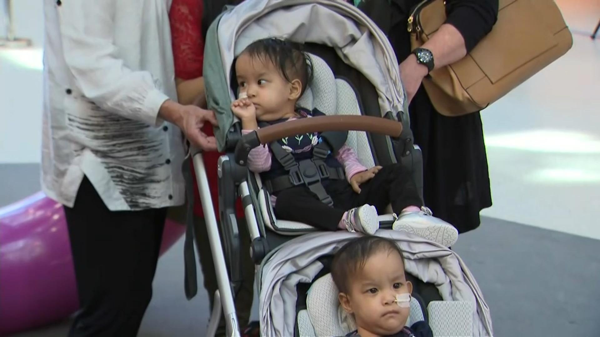 Bhutanese twins Nima and Dawa are wheeled out of hospital.