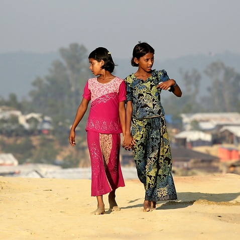 Rohingya refugee girls return to their tents at the Balukhali camp in Ukhiya, Bangladesh.
